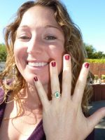 Woman smiling with emerald Calla Gold Jewelry designed wedding ring.