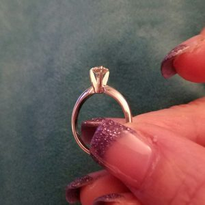 fingers holding solitaire ring