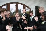 groom showing off his wedding band to his excited male friends