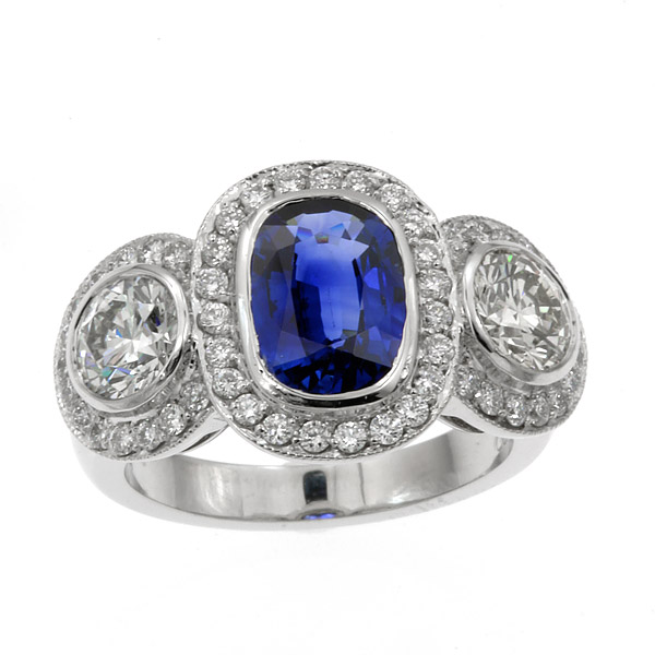 Cushion-cut-blue-sapphire-with-two-side-diamonds-and-halos-ring