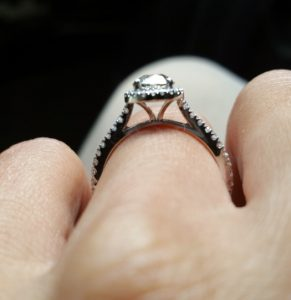Side view of engagement ring with halo of diamonds