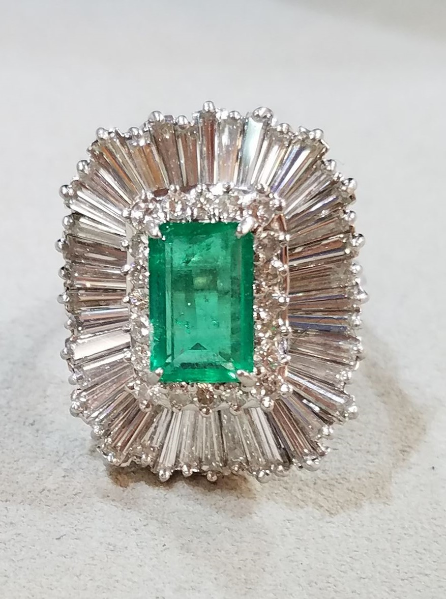 Ballerina setting ring with baguette diamonds surrounding an emerald
