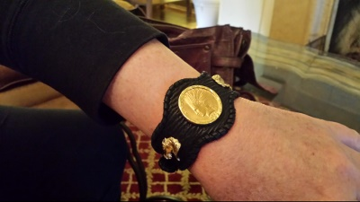 Woman wearing a leather bracelet with watch strap like closure. Leather bracelet with gold horses and coins