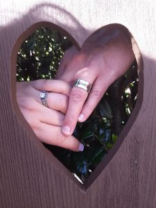 Man and woman's hand shown framed by wooden heart cut out. Man's wedding band has enamel design