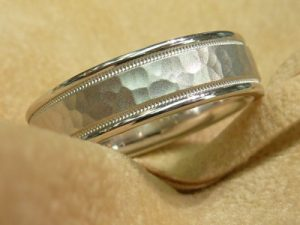 Man's white gold wedding band with shiny edges, and recessed milgrain flanking a hammered and matted center area