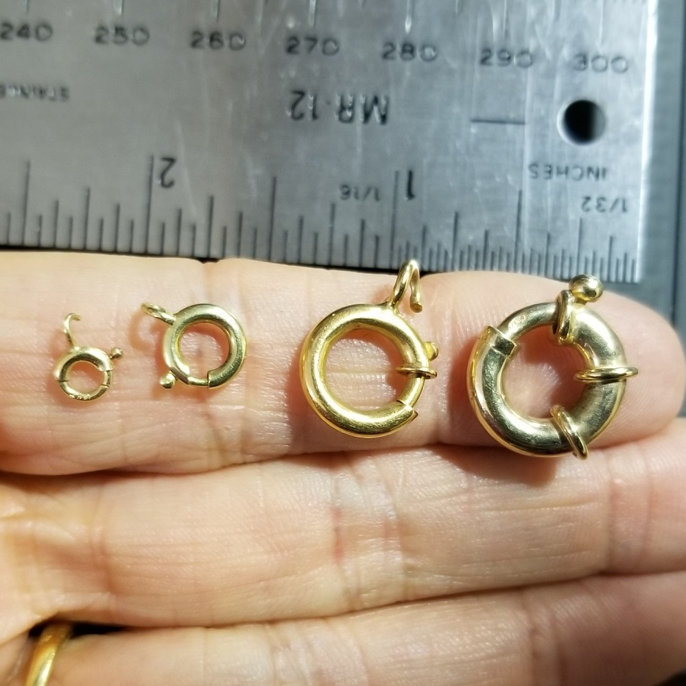 Selection of different sizes of spring ring clasps with a ruler for size comparison