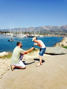 A man proposing to a woman at the Santa Barbara Harbor with a ring from the right jeweler