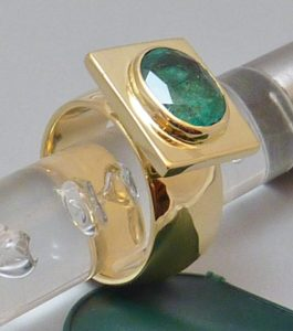 Emerald set in bezel with rectangular flat frame on wide band, ring