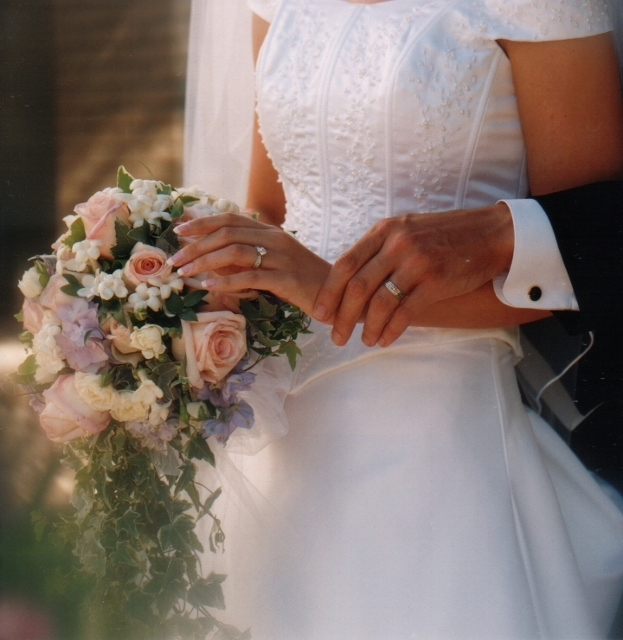 Bride and Groom's rings with standing couple