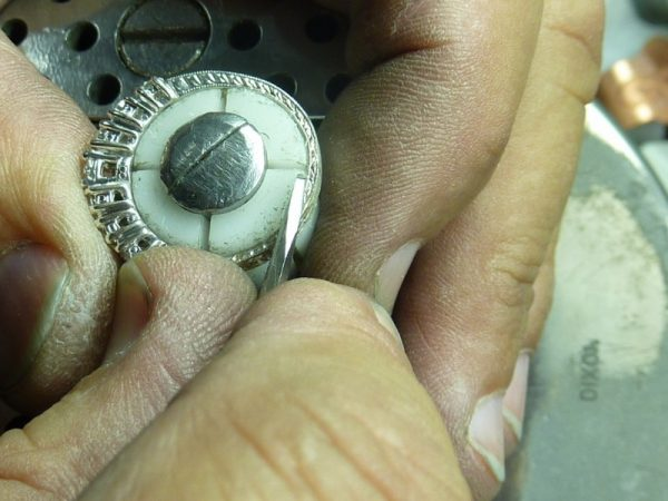 Close up of hands engraving a ring