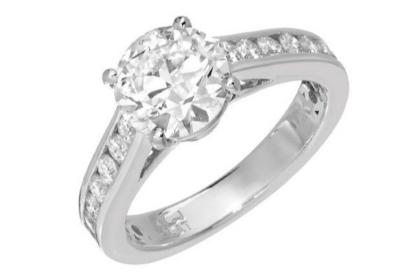 Four prong diamond engagement ring with channel set diamonds on the side. In 14kt white gold.