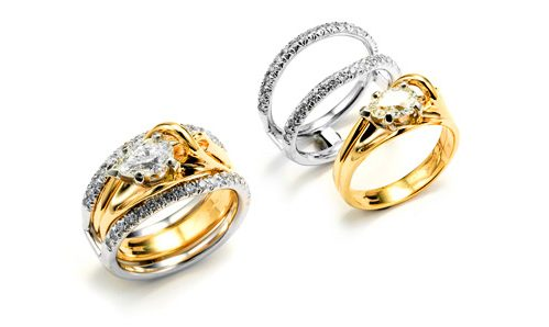 Three ring set. Two white gold and diamond rings are a guard. Center has a pear shaped diamond in yellow gold to contrast with the white gold